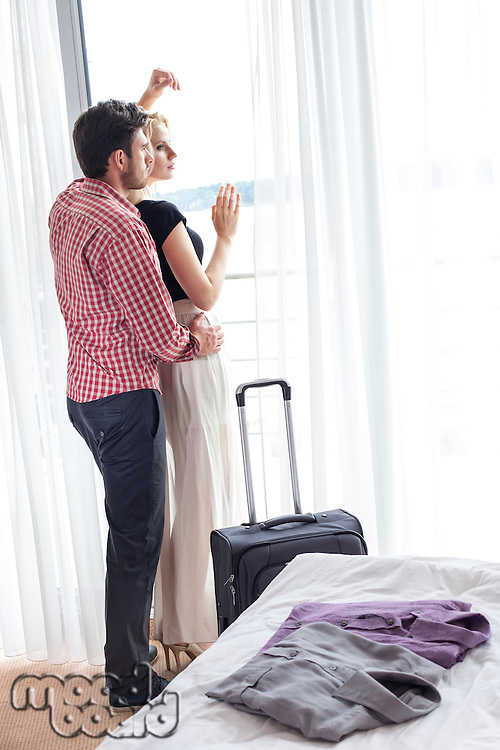 Full length of loving young couple looking through window in hotel room