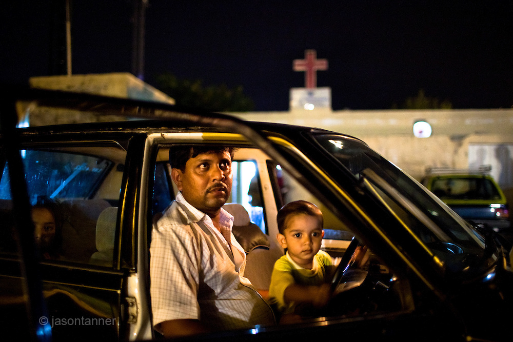 Islamabad: A taxi driver with his young son wait for customers outside the Gospel Assembly Church, one of several churches at the Christian colony in Islamabad...Pakistan's Christian communities account for an estimated one percent of the country's 180 million population...I the middle of Islamabad's wealthiest neighbourhood is a 'colony' that's home to some 4000 Christians. Narrow alleys separate multi-storey, squalid houses with open sewers running meandering the alleys to the river that runs through the heart of the colony...Some are recent arrivals from Faisalabad and Gojra, where recent sectarian killings forced many to relocate to the relative safety of the capitol territory. Many are second and third generation residents squatting on land that sees no development assistance from the Capital Development Authority. Power outages are frequent, many residents sleep on the roofs during the long summer months, there are no air-conditioners in the colony...Many of the residents are unemployed; those fortunate to have any income usually work as servants, gardeners, drivers, security guards or cleaners. ..Discrimination against the Christian minorities is rampant in Pakistani society. Many suspect the government of deliberately keeping them at the bottom of the economic ladder to appease the radical religious parties...©JTanner/August2011