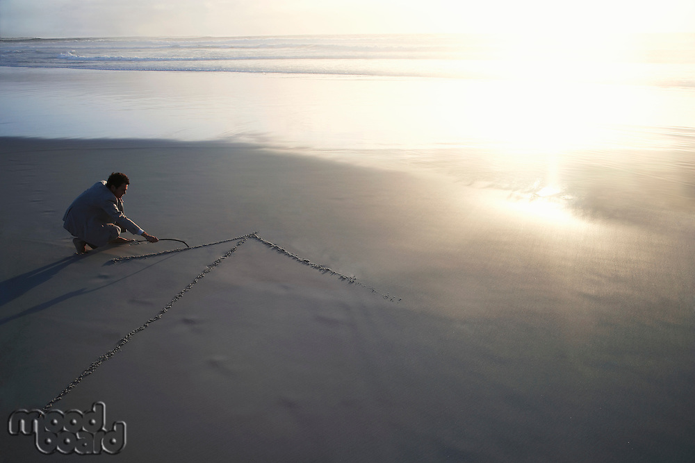Business man drawing arrow in sand on beach elevated view