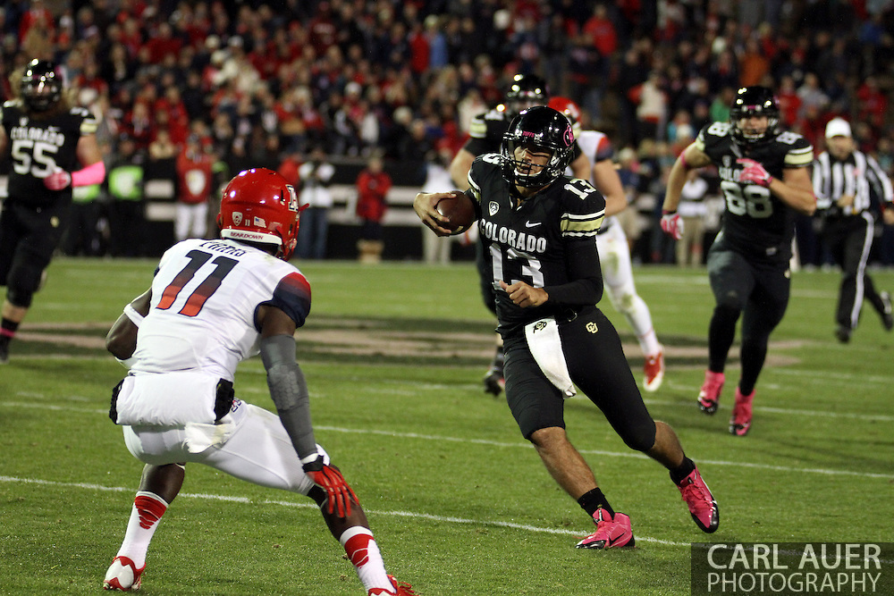 October 26th, 2013:  Colorado Buffaloes freshman quarterback Sefo Liufau (13) attempts to get past University of Arizona Wildcats sophomore safety William Parks (11) in the third quarter of the NCAA football game between the University of Arizona Wildcats and the University of Colorado Buffaloes at Folsom Field in Boulder, Colorado