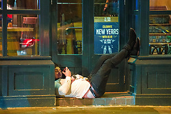 """© Licensed to London News Pictures . 16/12/2017. Manchester, UK. A man reclines in a doorway on Deansgate . Revellers out in Manchester City Centre overnight during """" Mad Friday """" , named for historically being one of the busiest nights of the year for the emergency services in the UK . Photo credit: Joel Goodman/LNP"""