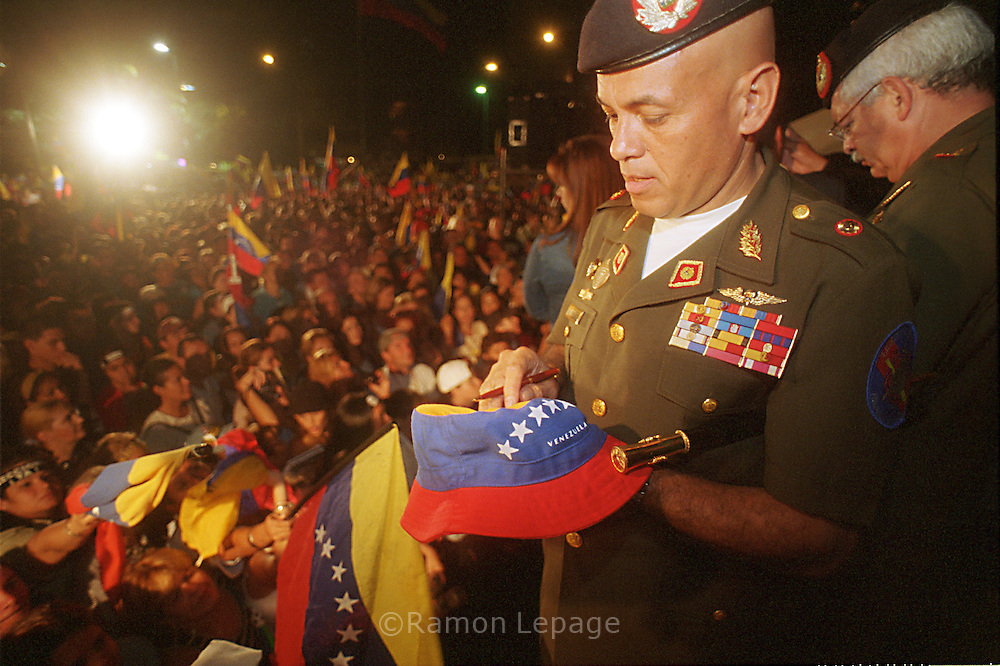 """El General disidente Néstor González González autografía una bandera durante protesta en Atamira. Manifestantes en la Plaza Francia de Altamira. Un grupo de 14 militares ocupan la Plaza Francia de Altamira el 22 de Octubre de 2002, para demostrar su rechazo al régimen del Presidente Hugo Chávez. Los días posteriores se van sumando más uniformados hasta completar 135 militares disidentes.  Un gran numero de personas acampa en los espacios de la plaza en apoyo al movimiento de """"resistencia civil"""",  que permanece en el lugar durante varios meses. Caracas,  octubre 2002. (Ramón Lepage / Orinoquiaphoto)  Néstor González González, disident militar signs a flag during a prostest in Altamira.   A group of 14 military occupy the Seat France in Altamira to demonstrate their rejection to the regime of President Hugo Chávez, the 22 of October of 2002. The later days more uniformed added until they complete 135 military dissident. A great number of people encamp in the spaces of the seat in support to the ?civil resistance? movement, which remains in the place during several months. Caracas, October 2002. (Ramon Lepage/Orinoquiaphoto)"""