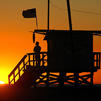 Los Angeles County Lifeguard William White, 34, watches as the sun sets for the last evening of the year at Santa Monica Beach on Monday, December 31, 2007. White has been a lifeguard for the past 12 years.