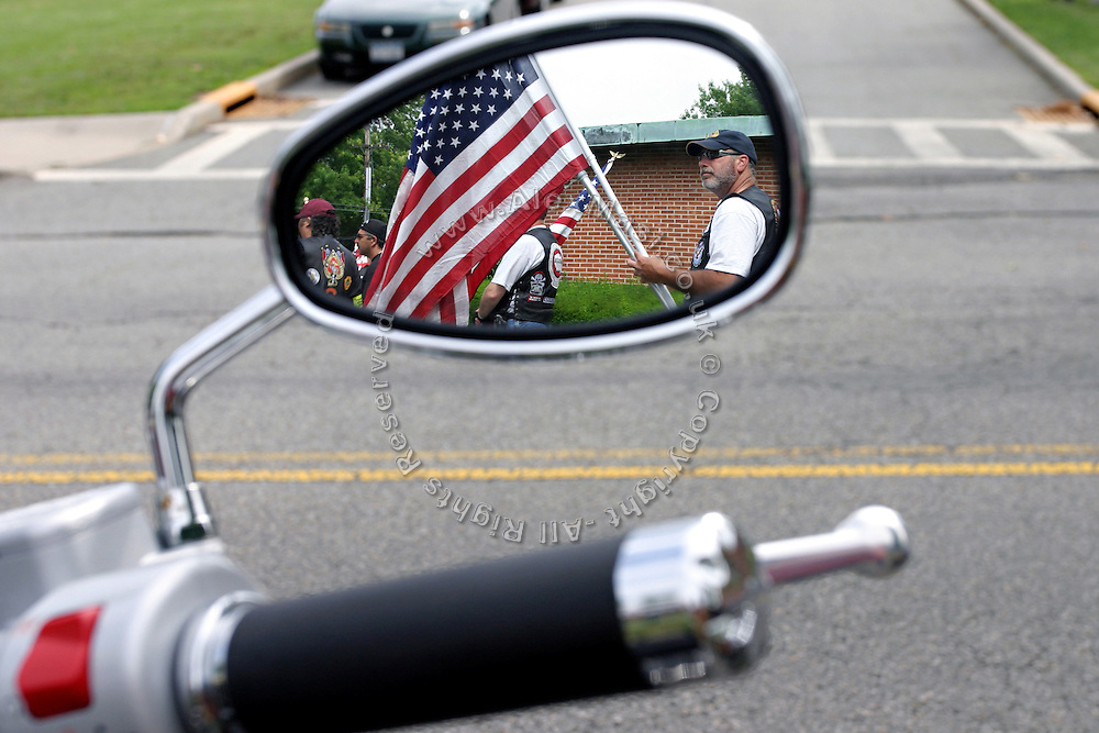 Members of the Patriot Guard Riders holding a US flag while awaiting for the start of the funeral service of Sgt. Ian T. Sanchez, in Staten Island, NY., on Tuesday, June 27, 2006. Sgt. Sanchez, a 26-year-old American serviceman was killed by a roadside bomb in the Pech River Valley, Afghanistan. The Patriot Guard Riders is a diverse amalgamation of riders from across the United States of America. Besides a passion for motorcycling, they all have in common an unwavering respect for those who risk their lives for the country's freedom and security. They are an American patriotic group, mainly but not only, composed by veterans from all over the United States. They work in unison, calling upon tens of different motorcycle groups, connected by an internet-based web where each of them can find out where and when a 'Mission' is called upon, and have the chance to take part. This way, the Patriot Guard Riders can cover the whole of the United States without having to ride from town to town but, by organising into different State Groups, each with its own State Captain, they are still able to maintain strictly firm guidelines, and to honour the same basic principles that moves the group from the its inception. The main aim of the Patriot Guard Riders is to attend the funeral services of fallen American servicemen, defined as 'Heroes' by the group,  as invited guests of the family. These so-called 'Missions' they undertake have two basic objectives in particular: to show their sincere respect for the US 'Fallen Heroes', their families, and their communities, and to shield the mourners from interruptions created by any group of protestors. Additionally the Patriot Guard Riders provide support to the veteran community and their families, in collaboration with the other veteran service organizations already working in the field.   **ITALY OUT**