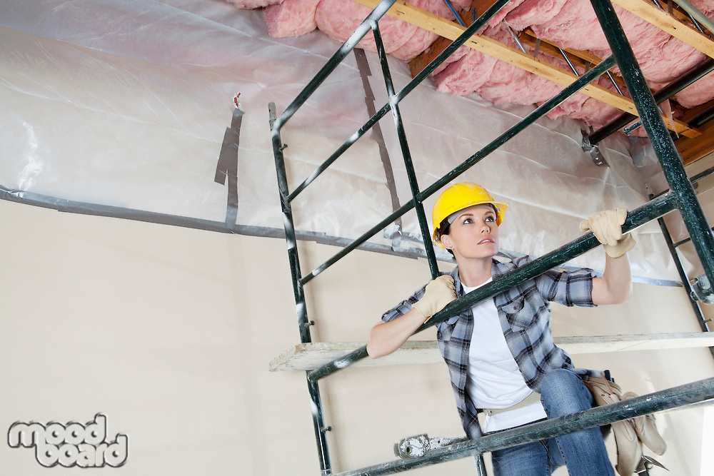 Female contractor climbing scaffold while looking away at construction site