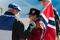 A man wearing a french flag stops to chat with a woman wearing traditional Norwegian clothing and carrying a flag during the 2010 Olympic Winter Games in Whistler, BC Canada.