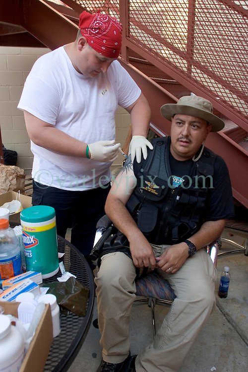 08 Sept 2005. New Orleans, Louisiana.<br /> <br /> Officer Ralf Gonzales of the Bernalillo County Sheriff's office in Albuquerque gets his hepatitis A and B and tetanus shots and health treatment from paramedics at a makeshift clinic at the 2nd precinct in uptown New Orleans.<br /> Photo; ©Charlie Varley/varleypix.com