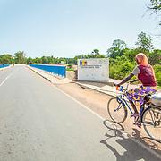 LÉGENDE: Une femme sur un vélo s'apprête à traverser un pont. Financé par la BAD. LIEU: Koumra, Tchad. PERSONNE(S): N/A.