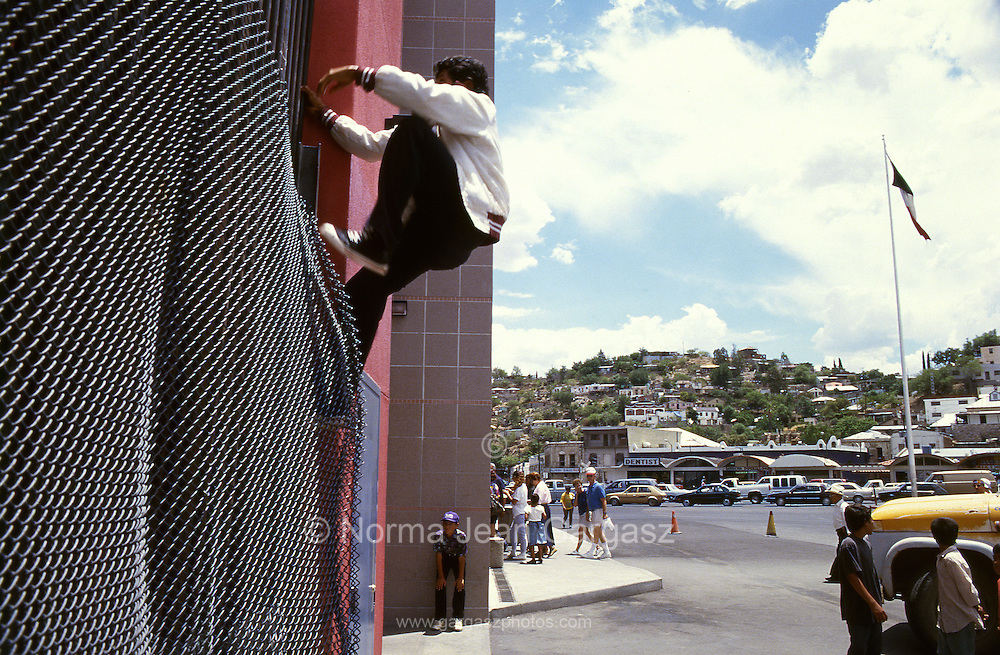 In a 1994 photo a man scales the border wall in Nogales, Sonora, Mexico, to cross illegally in to Nogales, Arizona, USA, at the U. S. Customs port of entry at the Mexican border.