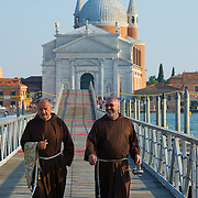 VENICE, ITALY - JULY 20:  Two friars wlk on the votive bridge ahead of the opening for the Redentore Celebrations on July 20, 2013 in Venice, Italy. Redentore is one of the most loved celebrations by Venetians which is in remembrance for the end of the 1577 plague. Highlights of the celebration include the pontoon bridge extending across the Giudecca Canal, gatherings on boats in the St Mark's basin and a spectacular fireworks display.  (Photo by Marco Secchi/Getty Images)