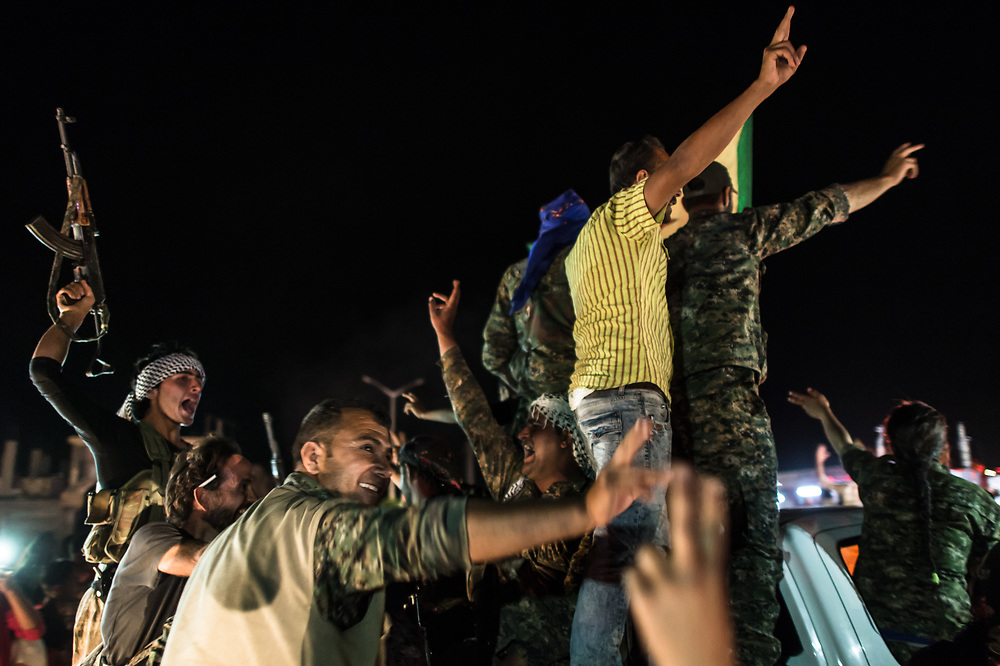 "In the streets of Kobanê, people are celebrating the capture of the city of Tell Abyad by the ""People's Defense Units"" / "" Women's Defense Units"" (YPG / YPJ) and their allies. The recapture of the territory that had been taken by ""Islamic State"" (ISIS) connects the cantons of Kurdish self-administration of Kobanê and Jazira. Kobanê (Ayn al-Arab), Syria, June 15, 2015"