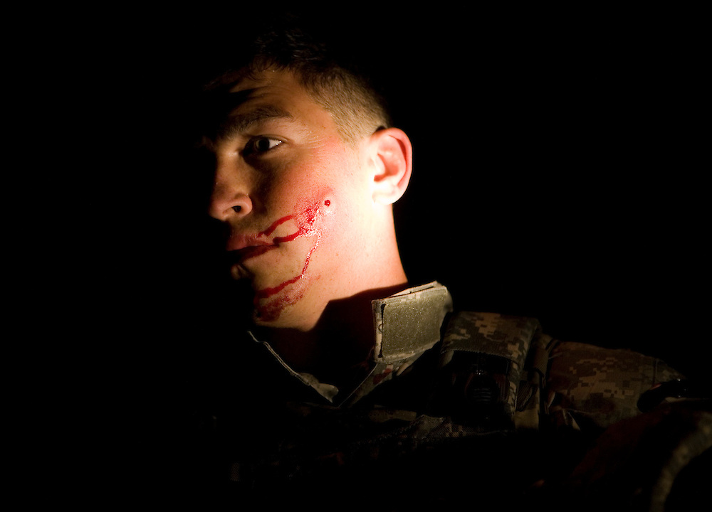 Specialist Shaun Hanna of the 82nd Airborne's 1/508 Parachute Infantry Regiment, Alpha Company, Third Platoon bleeds after being struck by shrapnel while breaching a door during a nighttime air assault into Sangin, Helmand province, the largest air assault in Afghanistan since the beginning of the war, on Thursday, April 5, 2007. Hanna was patched up by a medic, and immediately resumed the assault.