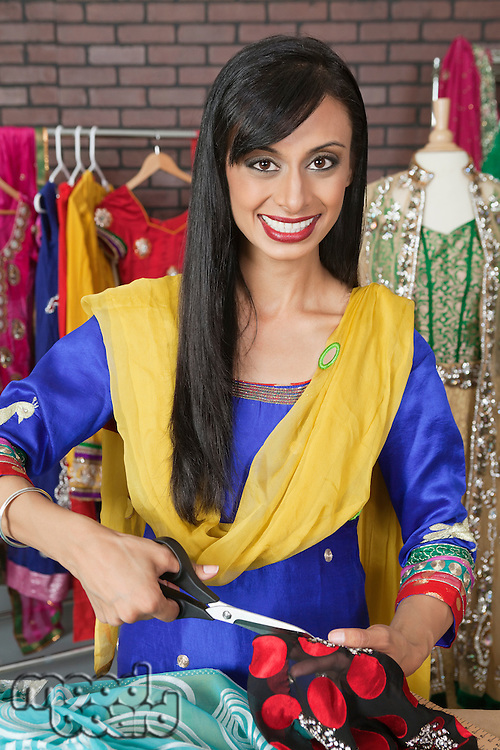 Portrait of an Indian female dressmaker cutting cloth