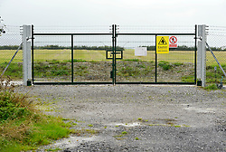 © Licensed to London News Pictures. 21/10/2013.  Hinkley Point, Somerset, UK.  Gates to land marked for building new Hinkley C at Hinkley Point Nuclear Power Station, which currently comprises the decommissioned Hinkley A station with Magnox Reactors (blue square buildings) and Hinkley B station (grey building complex, a more modern AGR design). The UK Government today announced the go-ahead for a new nuclear power station at Hinkley Point C in Somerset, to be built by a consortium with French firm EDF Energy and Chinese investment for the first time in UK nuclear power generation.21October 2013.<br /> Photo credit : Simon Chapman/LNP