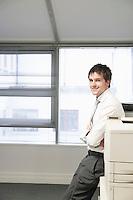 Businessman leaning against office photocopier portrait