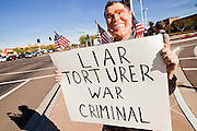 "09 DECEMBER 2010 - PHOENIX, AZ: VICTOR ARONOW, from Tempe, wears a George W. Bush mask while protesting in front of the Barnes & Noble Bookstore in Phoenix, AZ, Thursday, Dec. 9. More than 2,000 people lined up starting at 5AM to get copies of the former President's book, ""Decision Points."" A handful of protesters demonstrated against President Bush near the bookstore, calling him a ""war criminal.""   PHOTO BY JACK KURTZ"
