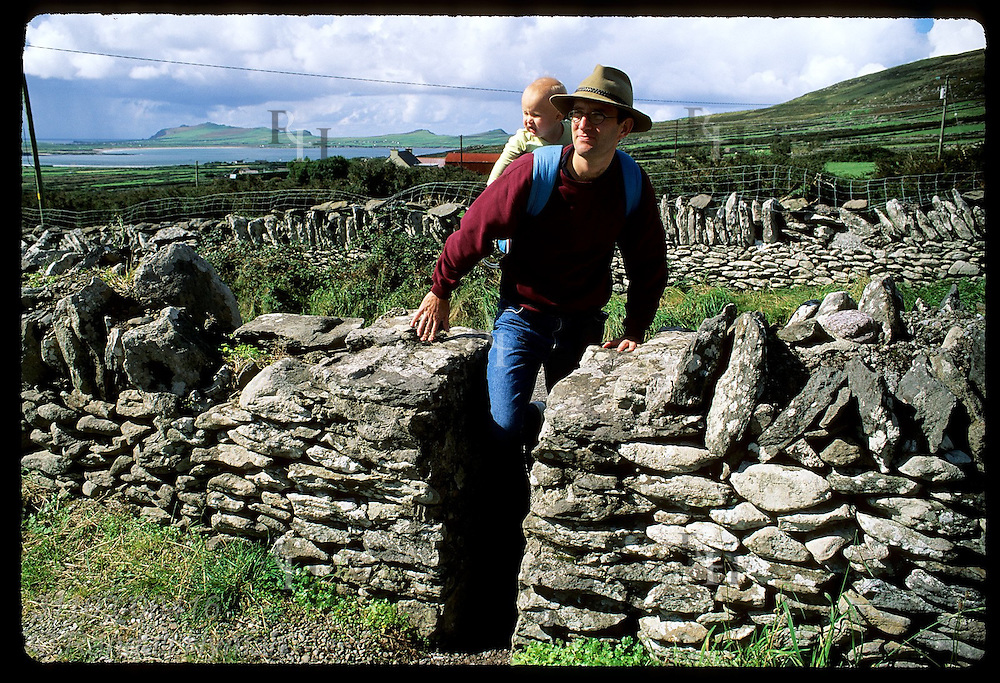 Man with baby in backpack steps thru notch in drystone wall at Kilmalkedar Church on the Dingle Peninsula in southwest Ireland.