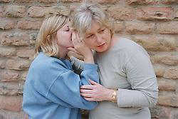 Teenage girl whispering in woman's ear,