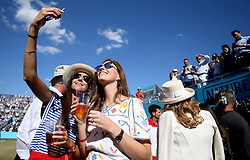 Spectators take a selfie as Novak Djokovic gives a TV interview after winning his match during day five of the Fever-Tree Championship at the Queen's Club, London.