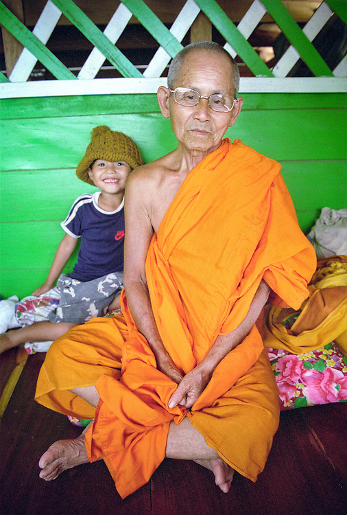 A monk and a playful young boy (the captain's son), on a boat going up the Mekong river, in the captain's quarters. Laos, 2003