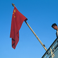 China, Jiangzi Province, Nanjing, Man stands by Chinese national flag aboard Yangtze River Ferry approaching Nanjing