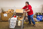 05 NOVEMBER 2013 - PHOENIX, AZ: STEVE PAWLAK, a volunteer at St. Mary's Food Bank in Phoenix, AZ, packs carts for clients. Demand at St. Mary's has continued to increase even as government assistance is reduced. Over the summer, St. Mary's Phoenix location provided emergency food for 300 - 400 families per day. They are currently supporting about 600 families per day. Part of the increase is seasonal but a large part of it is no clients coming to the food bank for the first time. More than 1.1 million Arizonans who use the Supplemental Nutrition Assistance Program, known as food stamps, saw their benefits reduced Friday, Nov. 1, in a long-planned national cut that was tied to the economic stimulus which was a part of the American Recovery and Reinvestment Act. The cuts imposed last week range from $11 a month for a single recipient to $65 or more for large families. Many of SNAP receipients already use food banks to supplement their government assistance and the cuts in the SNAP program are expected to increase demand even more.   PHOTO BY JACK KURTZ