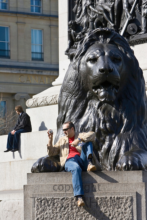 Tourist sits taking photographs on lion statues at base of Nelson's Column, Trafalgar Square, London, UK