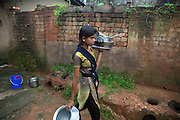 Tabasum Khatun, 14, is carrying some dishes to be washed in the courtyard of her home in Algunda village, pop. 1000, Giridih District, rural Jharkhand, India.