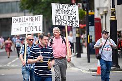 © Licensed to London News Pictures. 03/08/2019. LONDON, UK.  A protest by supporters of Stephen Yaxley-Lennon, known as Tommy Robinson, recently imprisoned after being found guilty of contempt of court, passes by Trafalgar Square, at the same time as thousands of members of the public take part in the Prudential RideLondon Freecycle event.  Photo credit: Stephen Chung/LNP