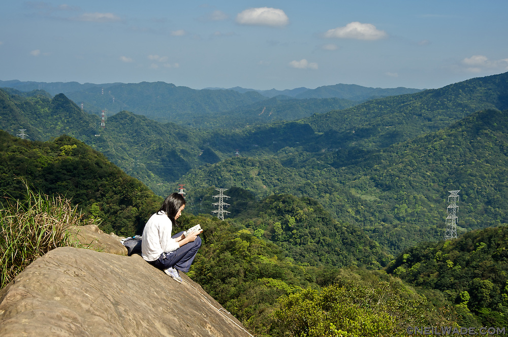A hiker reads a book high on an exposed mountain peak near Taipei, Taiwan.