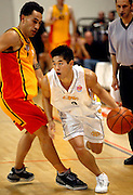 Bradley Moon bypasses Hawk number 32 Paul Henare during the NBL basketball match between the Wellington Saints and the Mighty Hawks, 14 April, 2002 at the Wellington Event Centre. Photo: PHOTOSPORT<br /><br /><br /><br />046432 *** Local Caption ***