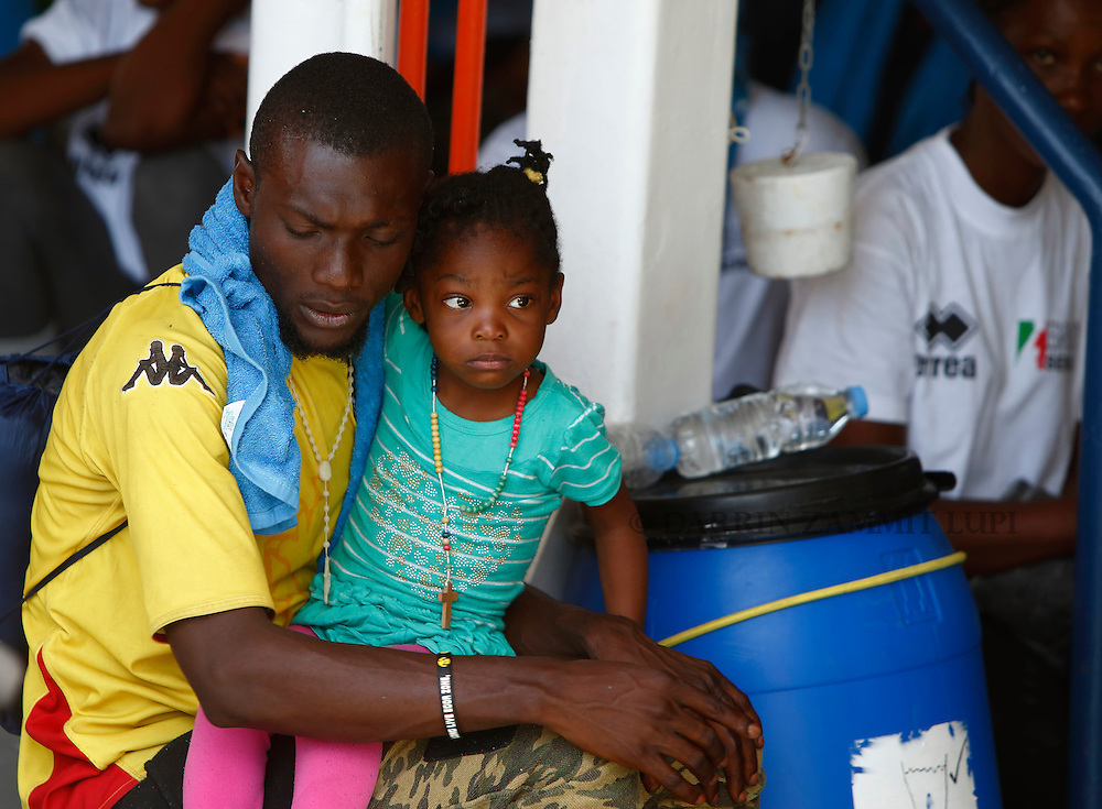 A sub-Saharan migrant holds his child while sitting on the deck of the Migrant Offshore Aid Station (MOAS) ship MV Phoenix in Vibo Valentia, Italy, July 31, 2015.  195 migrants who were rescued off Libya on Wednesday arrived in Italy on Friday afternoon. The Phoenix, manned by personnel from international non-governmental organisations Medecins san Frontiere (MSF) and MOAS, is the first privately funded vessel to operate in the Mediterranean.<br /> REUTERS/Darrin Zammit Lupi <br /> MALTA OUT. NO COMMERCIAL OR EDITORIAL SALES IN MALTA