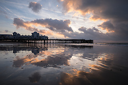 © Licensed to London News Pictures. 04/10/2016. Southsea, Hampshire, UK.  Reflections in the sand of the fiery sky as dawn breaks over South Parade Pier in Southsea this morning, 4th October 2016. Today will be another dry and sunny, but breezy, autumn day in the south of England. Photo credit: Rob Arnold/LNP