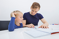 Mid adult man assisting boy in studies at table