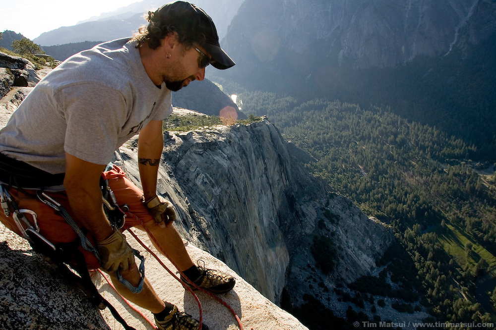 Rigger Ammon McNeely leans over a 1000m cliff at dawn on top of El Capitan for the filming of Am Limit, a Lotus Film production, about the climbing brothers Alexander and Thomas Huber and their attempt to break the speed climbing record on the Nose of El Capitan in Yosemite National Park, California, USA.