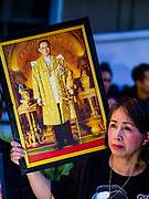 13 OCTOBER - BANGKOK, THAILAND: A woman holds a portrait of the late King while she waits for Buddhist monks on the first anniversary of the death of Bhumibol Adulyadej, the Late King of Thailand. About 199 monks from 14 Buddhist temples in Bangkok participated in the mass merit making at Siriraj Hospital to mark the anniversary of the revered King's death. He will be cremated on 26 October 2017.  PHOTO BY JACK KURTZ
