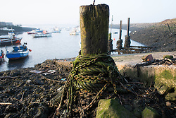 © Licensed to London News Pictures. 13/03/2014<br /> <br /> South Gare, Teesside, England, UK<br /> <br /> Old chains and ropes securing fishing boats are tied to a wooden post in an area known as South Gare at the mouth of the River Tees on Teesside.<br /> <br /> Photo credit : Ian Forsyth/LNP