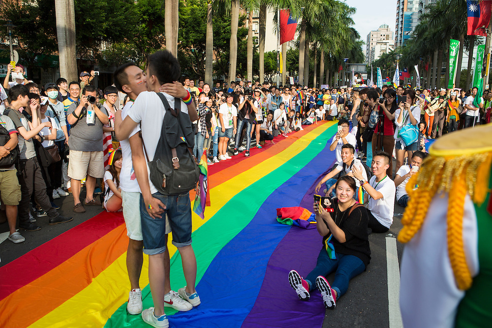 "Two gay men kiss standing on the rainbow banner, cheered on by an enthusiastic crowd at the pride parade. The annual march through Taipei's city streets is the largest in Asia, with well over 50 000 people taking part. The 2014 event had the theme ""Walk in Queer's Shoes"", to encourage the wider community to lend their support for equal marriage rights."