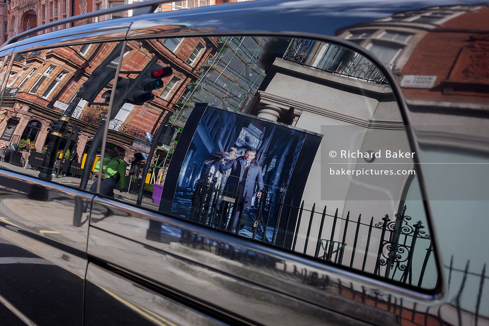 Reflected in a limousine car window is a construction hoarding featuring a male with a bird of prey on his arm, in Mayfair, central London, England.