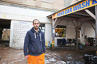 Employee washing vehicle at car wash
