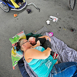 Tealla Dilka plays with her 18 month old son David as they lay on the asphalt underneath the 16th Street bridge in Boise, Idaho.  With complaints about the number of homeless people and the problems that arise when large numbers of homeless are in one place — on the rise, the city of Boise is taking steps to stop people from squatting near the skate park area.Wednesday June 25, 2014