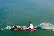 """Nederland, Noord-Holland, Gemeente Schoorl, 05-08-2014; Camperduin, Hondsbossche en Pettemer Zeewering. De zeewering is een van de Zwakke Schakels in de kust. Om de dijk te beschermen wordt er door middel van zandsuppletie een strand aangebracht voor de dijk.<br /> De zandsuppletie wordt onder andere uitgevoerd door middel van 'rainbowen', het in zee spuiten van zand+water. Op de foto de sleephopperzuiger Volvox Olympia.<br /> Camperduin, Hondsbossch and Petten dam. The seawall is one of the weak links in the coast. To protect the dike, sand nourishment is used to create a protecting beach.<br /> The sand replenishment is carried out  through """"rainbowing ', spraying sand + water into the sea. The photo shows the trailing suction hopper dredger Volvox Olympia.<br /> luchtfoto (toeslag op standard tarieven);<br /> aerial photo (additional fee required);<br /> copyright foto/photo Siebe Swart"""
