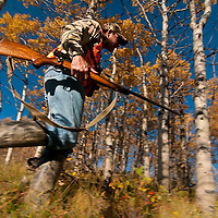 action deer hunter moving though the fall aspen trees close up low angle sky and motion