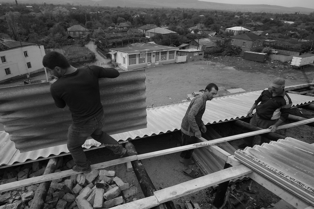 Construction workers repairing a roof in Karaleti, located in the so called bufferzone between Gori and Tskhinvali, few days after the withdrawal of the russian forces from the area. The bufferzone was etablished after a short war in August 2008 as the georgian army assulted South Ossetia to overthrow the local separatist government.