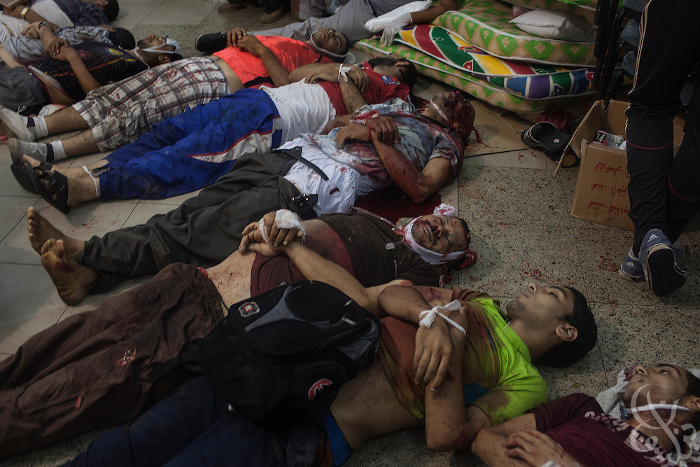 The bodies of at least 9 pro-Morsi supporters lie on a floor at a field hospital inside the Rabaah al-Adawiya protest camp in Nasr City, Egypt during the August 14, 2013 Ministry of Interior/Police operation to clear the more than month long protest by force. The assault, which began at 7am with police moving in to seal the surrounding streets included tear gas and live fire, and there are reports of large numbers of killed and wounded protesters.