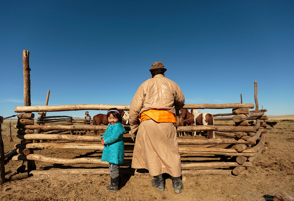 Delgr Tuya and her grandfather inspect the family horses in a corral near their nomad ger tent.