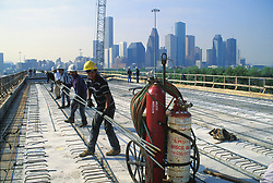 Stock photo of men hauling rebar on the top of a newly constructed building just outside of downtown Houston Texas