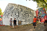 """Huntington, New York, U.S. 24th August 2013. Three world renowned street artists are decorating with graffiti the rear walls of the Hunting Arts Council building, at the art event """"Off the Walls"""" Block Party, by SPARKBOOM, a project the council created to help emerging artists, showcase talents, and help its artistic family network. Taken with 180 degree fisheye lens."""