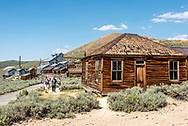 People explore Bodie State Historic Park with the Standard Consolidated Mining Company Stamp Mill in the background and an old wooden house beside them.