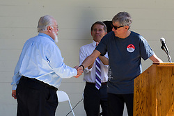 10 May 2014:  Normal Mayor Chris Koos shakes hand of Garrett Scott for 25th anniversary celebration of the Constitution Trail ceremony at Connie Link Amphitheater in Normal Illinois